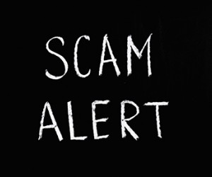 Scam aler written on chalboard
