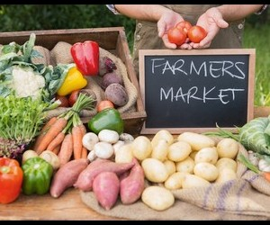 A Farmers Market sign with various vegetables