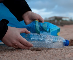 Picking up a plastic bottle off of a beach