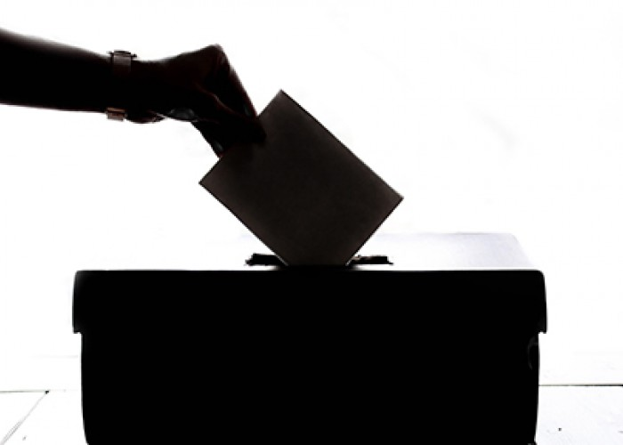 Person hand holding a ballot and dropping it into a ballot box.