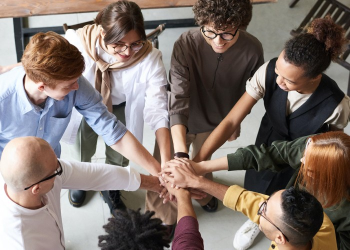 Picture of people in a circle expresing teamwork in the workplace